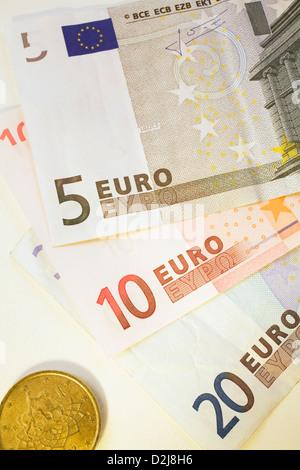 Nahaufnahme von Euro-Banknoten der Bank und eine Münze auf einem weißen Hintergrund - Stockfoto