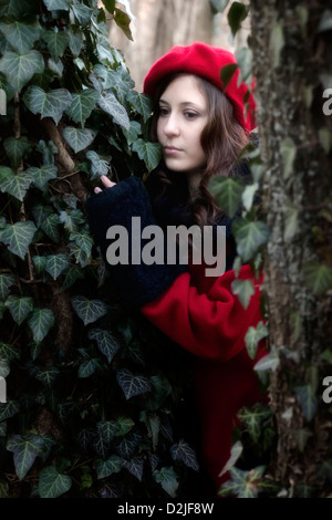 eine Frau mit einem roten Mantel und Hut zwischen zwei Stämmen - Stockfoto