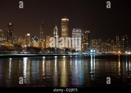 Nacht-Blick auf die Skyline von Chicago mit Lake Michigan im Vordergrund - Stockfoto