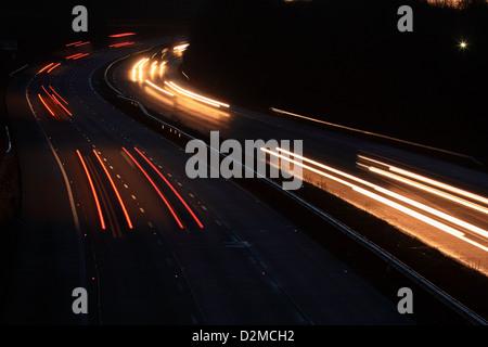 Lichtspuren verursacht durch Fahrzeuge fahren auf der Autobahn M20 früh am Morgen. - Stockfoto