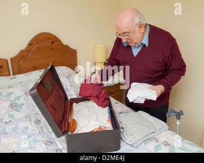 älterer Mann Kleidung in den Koffer packen, vielleicht verlassen für ...