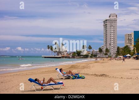 SAN JUAN, PUERTO RICO - Frauen-Touristen, die gerne bei Smartphones am Strand von Isla Verde. - Stockfoto
