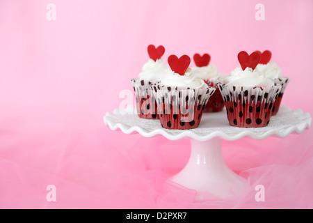 Red velvet Cupcakes mit Cream Cheese frosting mit roten Schokolade Herzen verziert. Kopieren Sie Platz auf der Seite. - Stockfoto