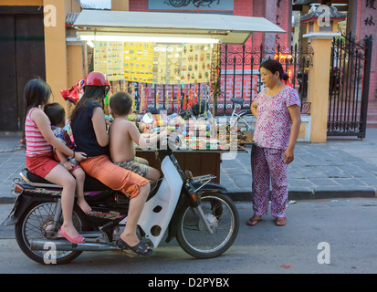Kinder vorbeischauen auf ihr Motorrad anzusehen Schmuckstücke verkauft werden, von einer Frau mit einem Push Cart, - Stockfoto