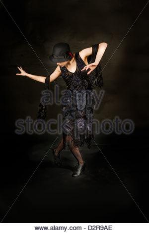 Frau tanzt in einem 1920 Perlen Flapper Kleid in Sepia getönt schwarz und weiß. - Stockfoto