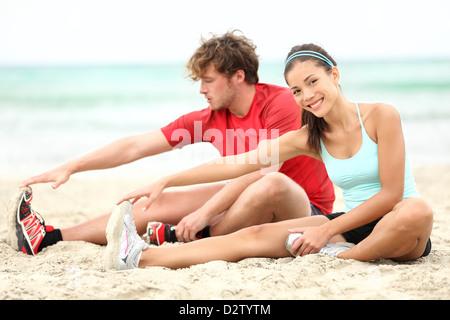 Junge Sitz paar stretching Beine nach dem laufen am Strand während des Sommer-Trainings - Stockfoto