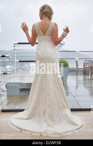 Eine hübsche junge blonde Braut suchen aus einem Fenster heraus, wie sie für ihre Trauung wartet. - Stockfoto