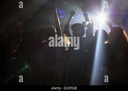 Scheinwerfer über Silhouette der Menge jubeln beim Konzert - Stockfoto