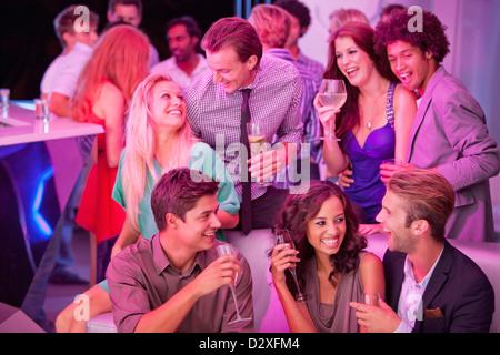 Lächelnden Freunde trinken Champagner in Nachtclub - Stockfoto