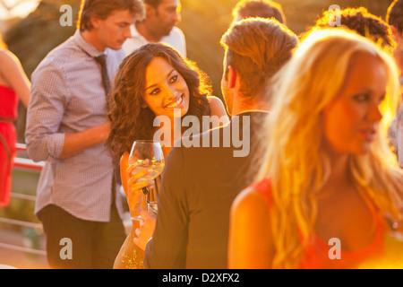 Lächelnde Frau mit Weinglas Gespräch mit Mann auf sonnigen Balkon - Stockfoto
