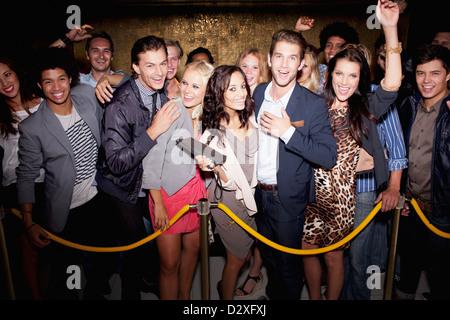Porträt der begeisterten Menge in Warteschlange vor Nachtclub - Stockfoto