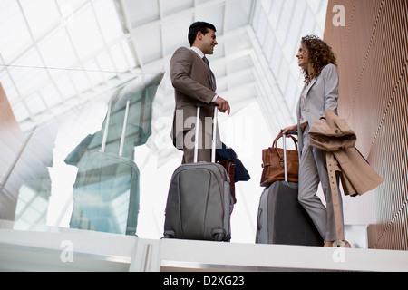 Lächelnd Geschäftsmann und Geschäftsfrau mit Koffer im Flughafen im Gespräch - Stockfoto