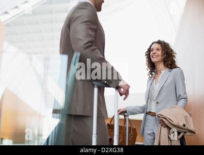 Lächelnde Geschäftsfrau im Gespräch mit Geschäftsmann in Flughafen - Stockfoto