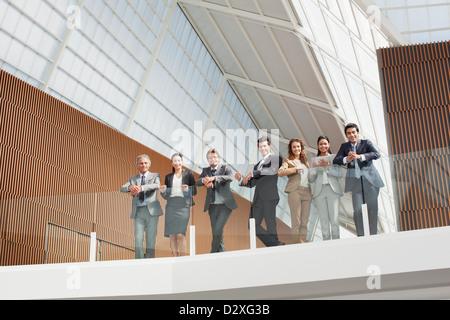 Porträt des Lächelns Geschäftsleute auf Balkongeländer gelehnt - Stockfoto