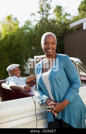 Lächelnde ältere Frau stützte sich auf Cabrio - Stockfoto
