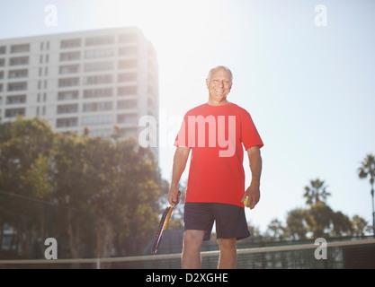 Älterer Mann mit dem Tennisspielen auf Platz - Stockfoto