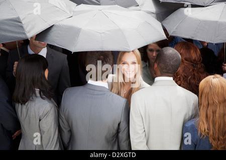 Porträt von lächelnden Geschäftsfrau umgeben von Masse mit Sonnenschirmen - Stockfoto