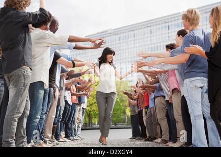 Frau, die Hände der Fans im Publikum zu berühren - Stockfoto