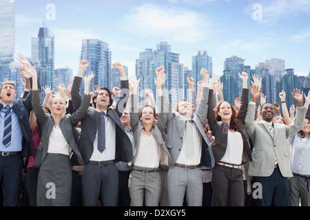 Business-Leute jubeln mit vor Skyline erhobenen Armen - Stockfoto