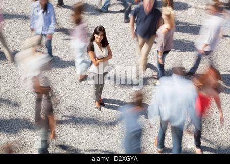 Porträt der selbstbewusste Frau stehend unter rauschenden Menge - Stockfoto
