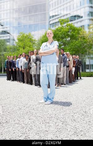 Porträt von zuversichtlich Krankenschwester mit Geschäftsleuten im Hintergrund - Stockfoto