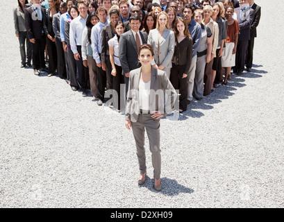 Porträt von zuversichtlich Geschäftsfrau mit Team von Geschäftsleuten im Hintergrund - Stockfoto