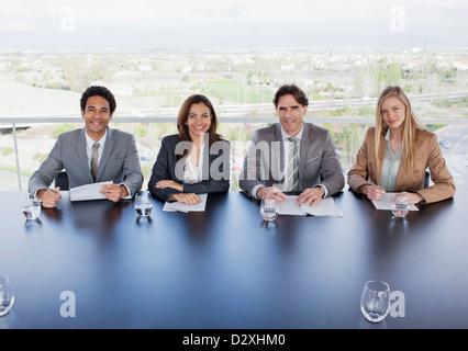 Porträt des Lächelns Geschäftsleute sitzen am Tisch im Konferenzraum - Stockfoto