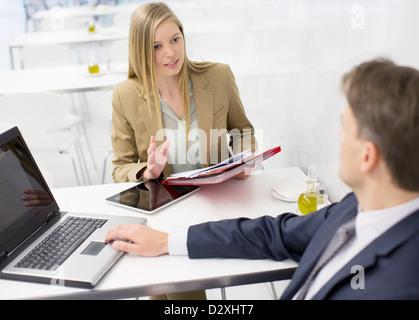 Unternehmer und Unternehmerin diskutieren Papierkram - Stockfoto