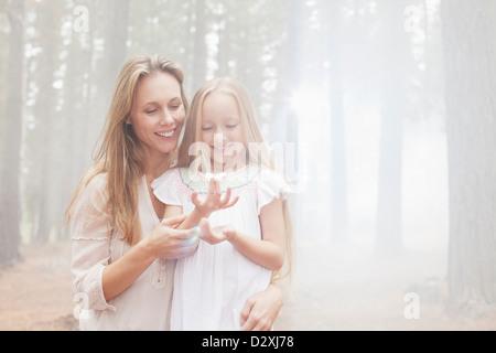 Lächelnde Mutter und Tochter im sonnigen Wald - Stockfoto