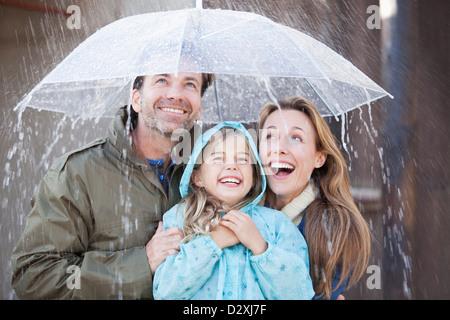 Begeisterte Familie unter Dach im Regen - Stockfoto