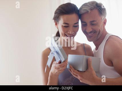 Lächelndes Paar öffnen Geschenkbox - Stockfoto