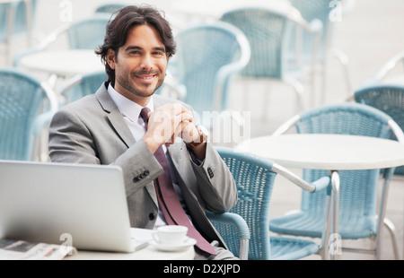 Porträt von lächelnden Geschäftsmann mit Laptop und Espresso im Straßencafé - Stockfoto