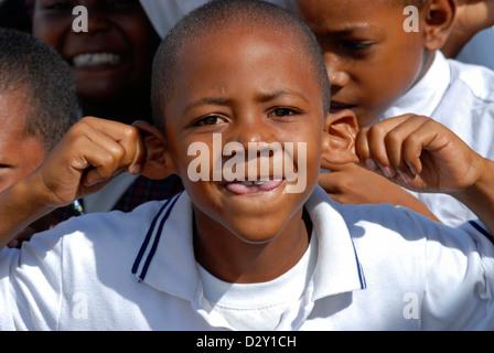 Kolumbien, Tierrabomba, Nahaufnahme von Schuljunge zieht seine Ohren mit Freunden im Hintergrund - Stockfoto