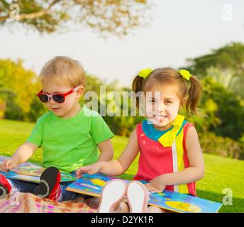 Kinder lesen Sie Fotobuch im Freien in der Kindertagesstätte, zwei glückliche Kinder freuen sich über Märchen, Bruder und Schwester, die Lektion zu studieren Stockfoto