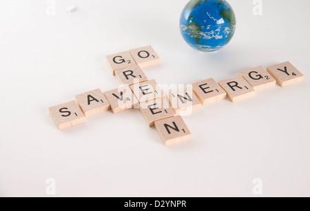 """""""Sparen Energie, Go Green"""" Konzept geschrieben in Scrabble Buchstaben mit aus Fokus Weltkugel im Hintergrund. Isoliert - Stockfoto"""