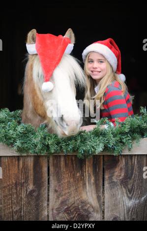 Mädchen und Pferd mit Santa Hüte im Stall Fenster für Weihnachten, süße junge Blondine, die zehn Jahre alt und ein - Stockfoto