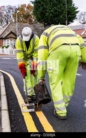 Die Beschäftigten im Straßenverkehr zur Festlegung der doppelten gelben Linien Fahrbahnmarkierungen auf einer Straße, - Stockfoto