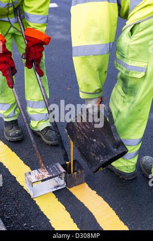 Die Beschäftigten im Straßenverkehr Malerei doppelten gelben Linien Fahrbahnmarkierungen auf einer Straße, Großbritannien - Stockfoto