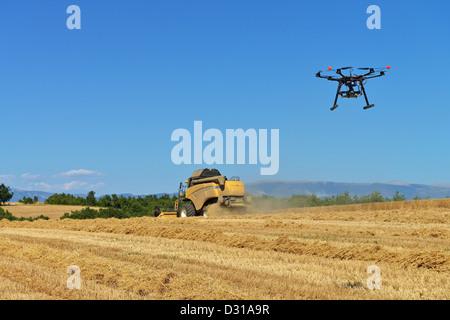 Drone - Unmanned Aerial Vehicle (UAV) Fotografieren / Filmen Mähdrescher im Weizenfeld im Sommer, Frankreich - Stockfoto