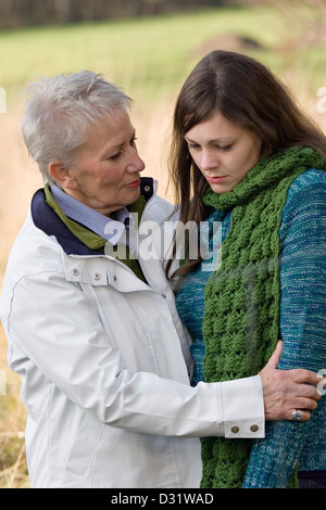 Ältere Frau tröstet ihre Tochter erwachsen - Stockfoto