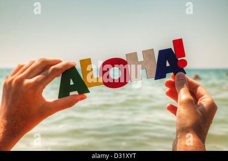 """Weiblichen Hand mit bunten Wort """"Aloha"""" vor blauem Hintergrund - Stockfoto"""