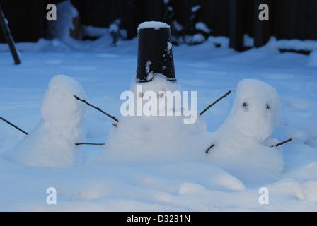 drei kleine Schneemänner im Schnee als es dunkel wird von Kindern mit einem Eimer für einen Hut gemacht und für - Stockfoto