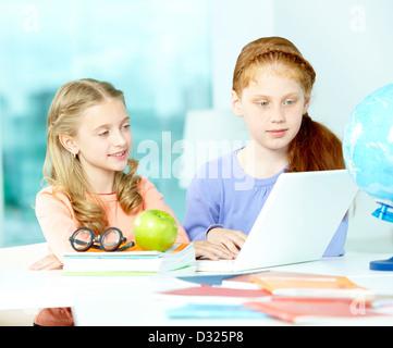 Porträt von smart Schülerinnen sitzen im Klassenzimmer vor laptop - Stockfoto