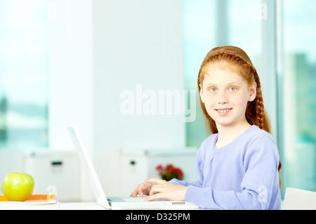Porträt von smart Schulmädchen im Klassenzimmer sitzen und schreiben - Stockfoto