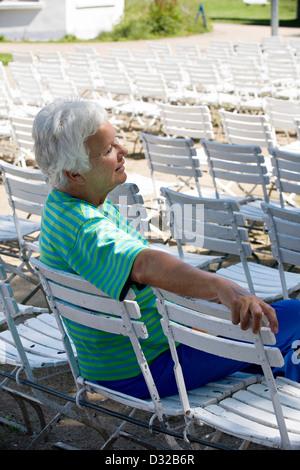Ältere Dame sitzt auf einem Stuhl im Kurpark - Stockfoto