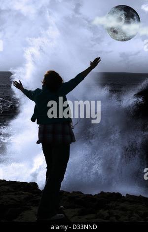 eine einsame Frau, hob die Arme in Ehrfurcht vor der mächtige Welle und Vollmond am Rande der Klippen in County - Stockfoto