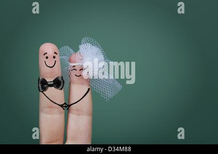 Zwei glückliche Finger als Braut und Bräutigam mit Schleier und Fliege verziert - Stockfoto