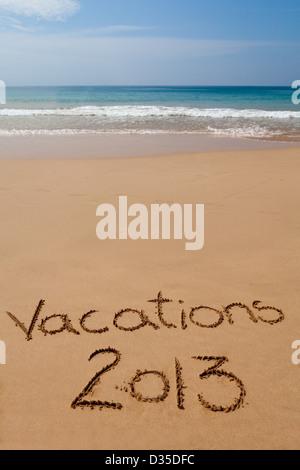 """Worte """"Ferien 2013"""" geschrieben in Sand am tropischen Strand - Stockfoto"""