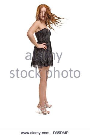 Teen Mädchen in einem Kleid mit roten Haaren stehen auf einem weißen Hintergrund in Highheels in die Kamera schaut. - Stockfoto