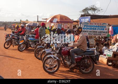 Kamerun, 2. Oktober 2012: Motorrad-Taxis warten auf Passagiere in einer neuen Kleinstadt im Wald. - Stockfoto